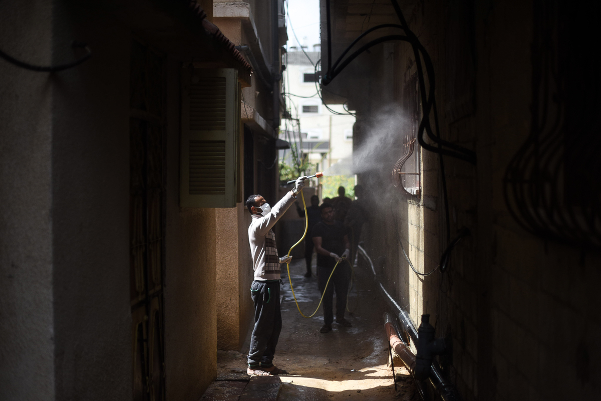 A volunteer disinfects buildings in the village of Khuza'a using a chlorine solution. [Abed Zagout/ICRC]