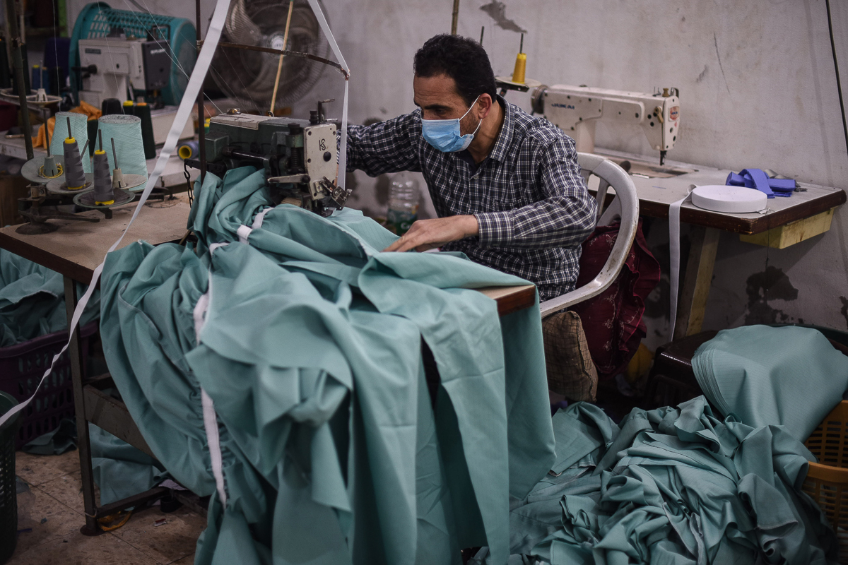 A Palestinian worker makes protective clothing at a factory in Sheikh Radwan in Gaza City. [Abed Zagout/ICRC]