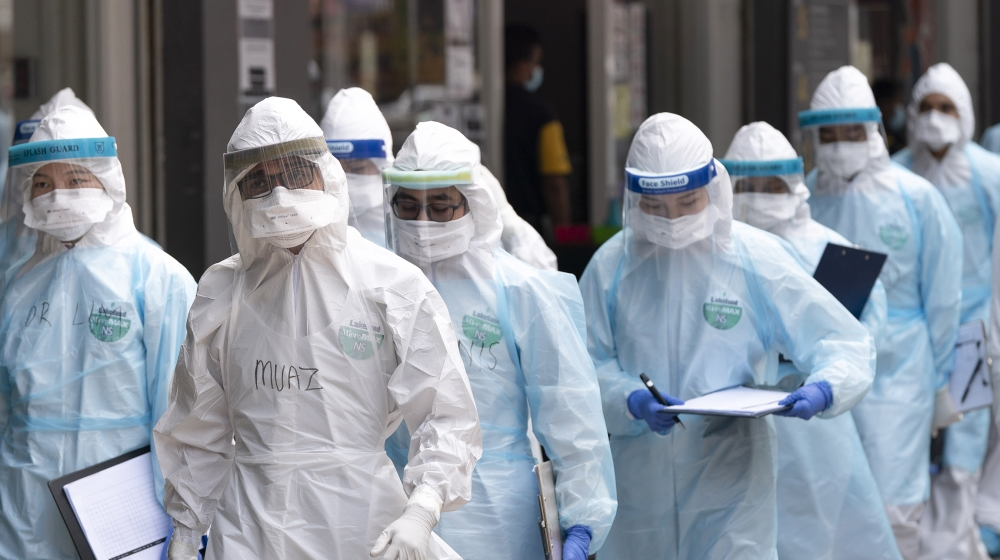 Medical workers in protective suits entering a building under lockdown in downtown Kuala Lumpur, Malaysia, on Tuesday, April 7, 2020. The Malaysian government issued a restricted movement order to the