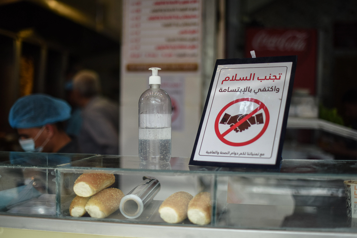 The owner of this restaurant in Khan Younis put out a sign to discourage people from handshakes, as well as a bottle of hand sanitiser. [Abed Zagout/ICRC]
