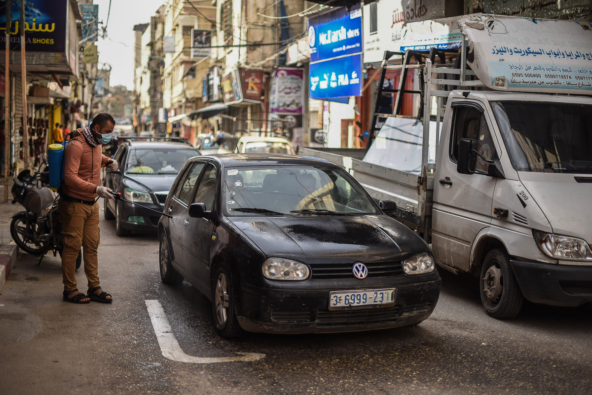 Young Palestinian volunteers disinfect streets and cars in Khan Younis. [Abed Zagout/ICRC]