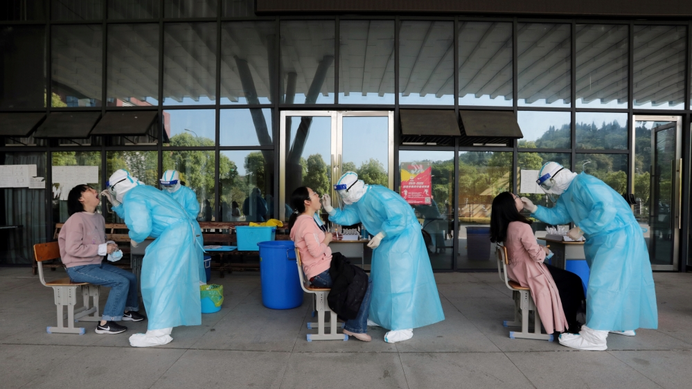 Medical workers collect swabs from high school teachers for nucleic acid tests at a school in Yichang