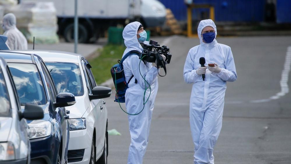 Journalists wearing protective gear wait near a quarantined hostel in Kiev