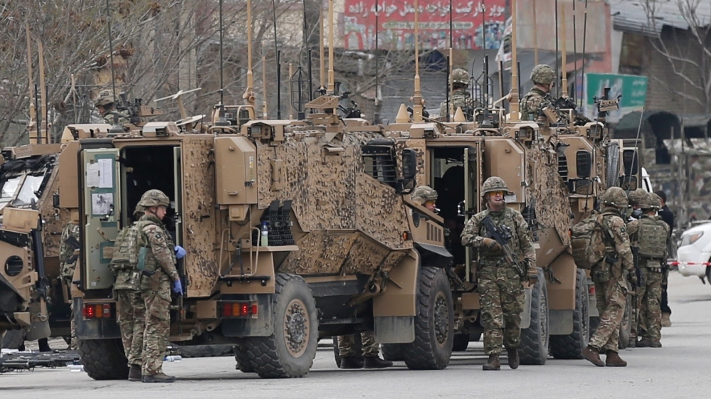 NATO soldiers inspect near the site of an attack in Kabul