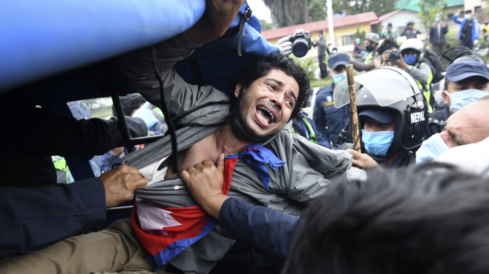 A demonstrator shouts slogans after he was detained by the police during a protest against India's newly inaugurated link road to the Chinese border, in Kathmandu on May 11, 2020. Nepal protested Ind