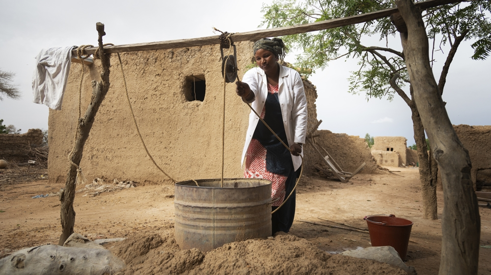 Salimata Dagnogo, 32, Matron of Talo Health Centre, collects dirty water from an open well in the village. Salimata has worked at Talo for eight years and faces big challenges in her role without the