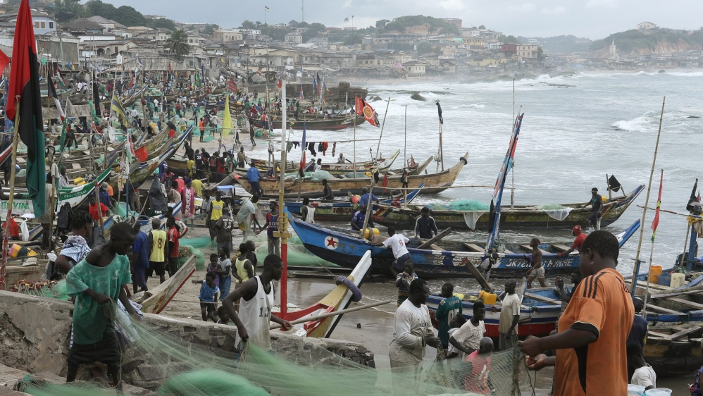 Fishermen tend their boats and fishing nets at Cape Coast
