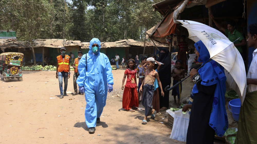 In this April 15, 2020, photograph, a health worker from an aid organization walks wearing a hazmat suit at the Kutupalong Rohingya refugee camp in Cox's Bazar, Bangladesh. There's been little if any