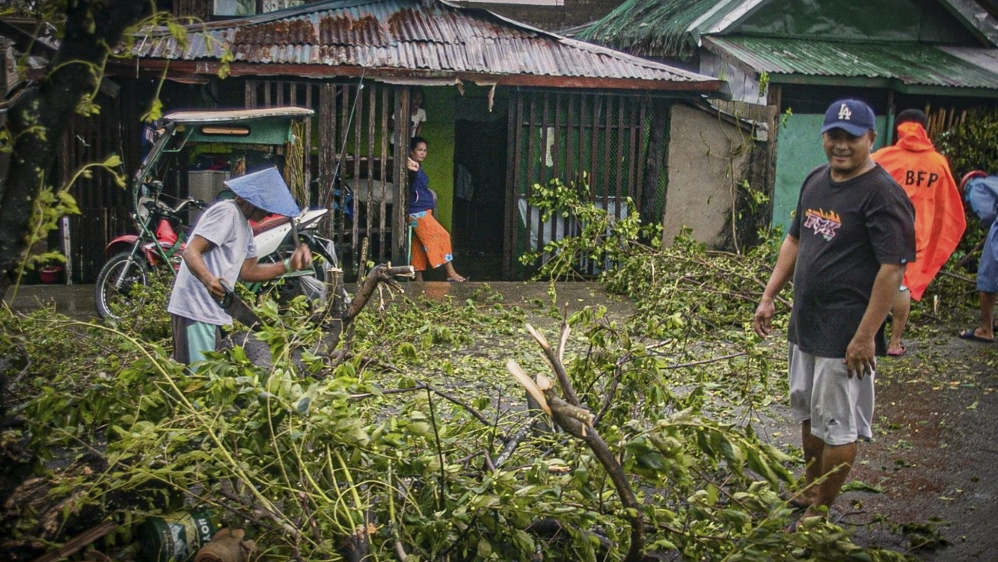 Citizens cut up a tree that has fallen on a road as Typhoon Vongfong makes landfall in the town of Can-avid, Eastern Samar province, the Philippines, 14 May 2020. The typhoon reached the Eastern Samar