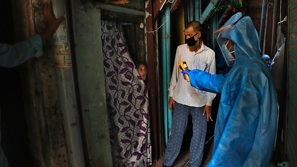 A doctor check the temperature of a girl in Dharavi, one of Asia's largest slums, during lockdown to prevent the spread of the new coronavirus in Mumbai, India, Monday, April 13, 2020. The new coronav