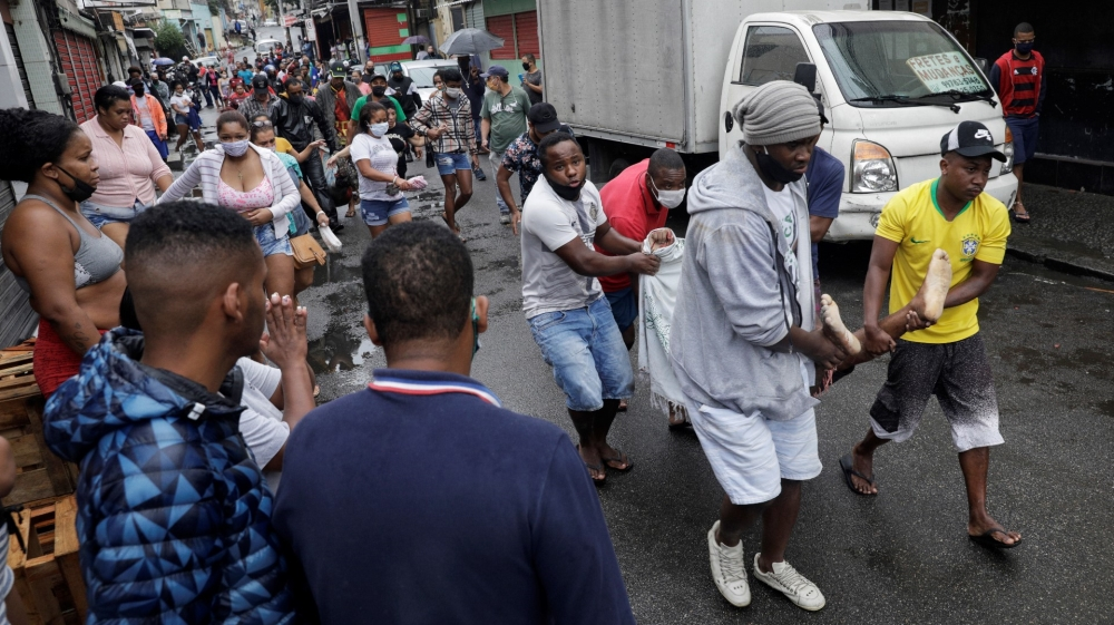 Residents carry a dead body after a police operation against drug gangs in Rio de Janeiro