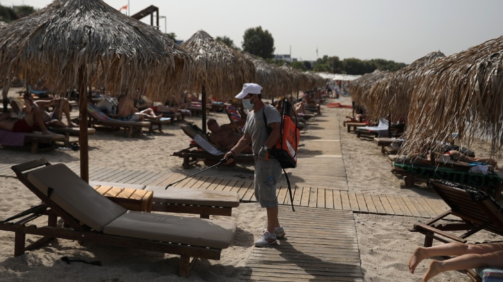 A man wearing a face mask disinfects a sunbed during the official reopening of beaches to the public following the easing of measures against the spread of the coronavirus disease (COVID-19),