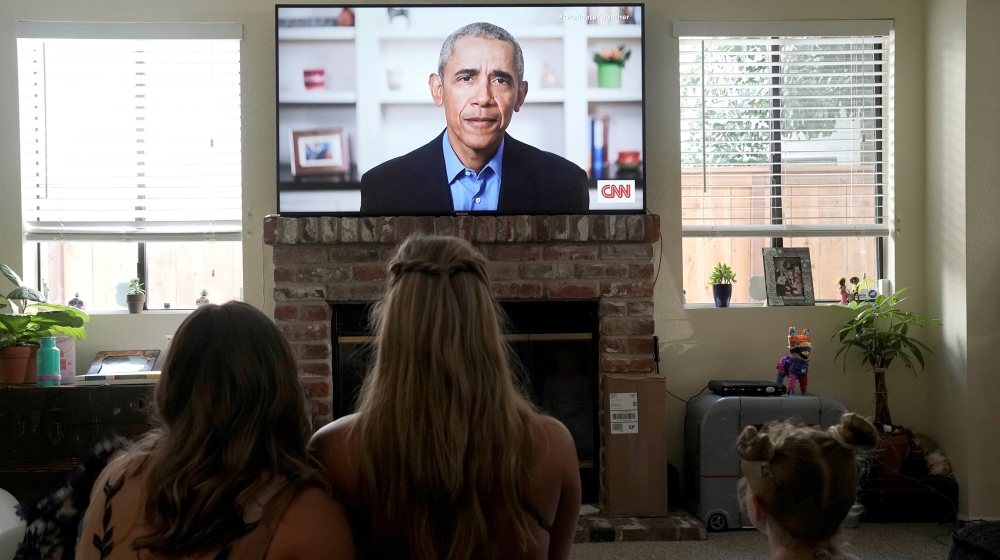 Torrey Pines High School graduating student Phoebe Seip (18, center), and her sisters Sydney (22, left) and Paisley, 6, watch former U.S. President Barack Obama deliver a virtual commencement address