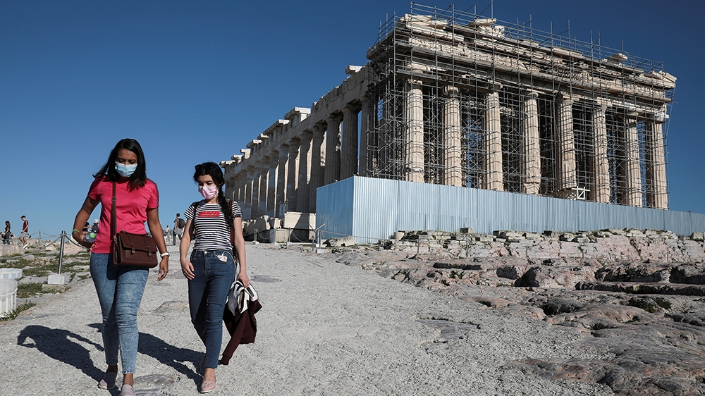 Visitors wear protective face masks as they walk past the ancient Parthenon temple at the archaeological site of the Acropolis in Athens, Greece, March 13, 2020. REUTERS/Costas Baltas