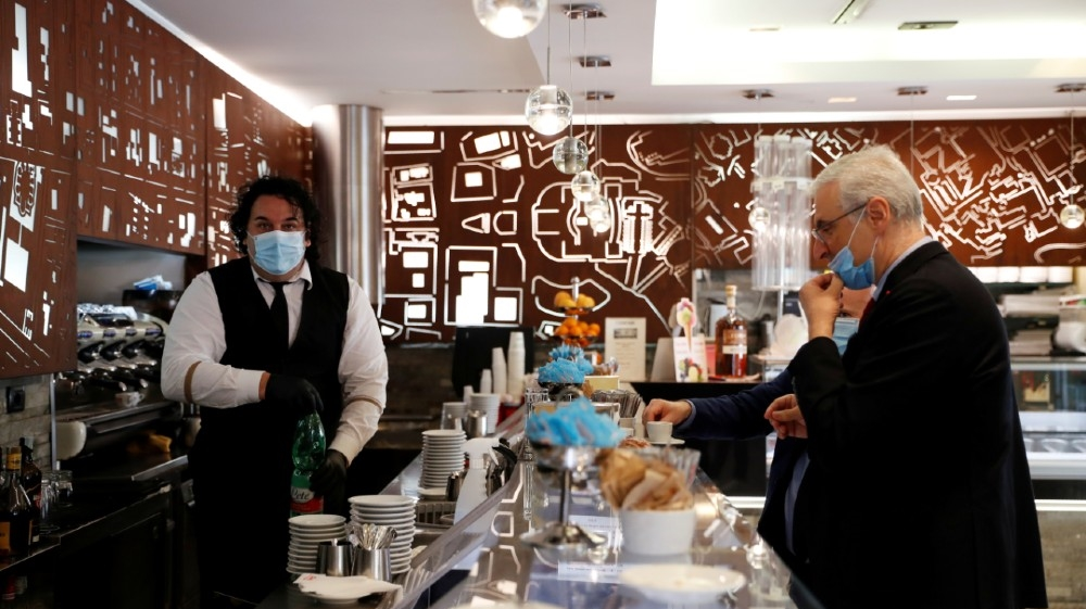 A man wearing a face mask serves a customer, as shops are allowed to reopen as Italy eases some of the lockdown measures put in place during the coronavirus disease (COVID-19)