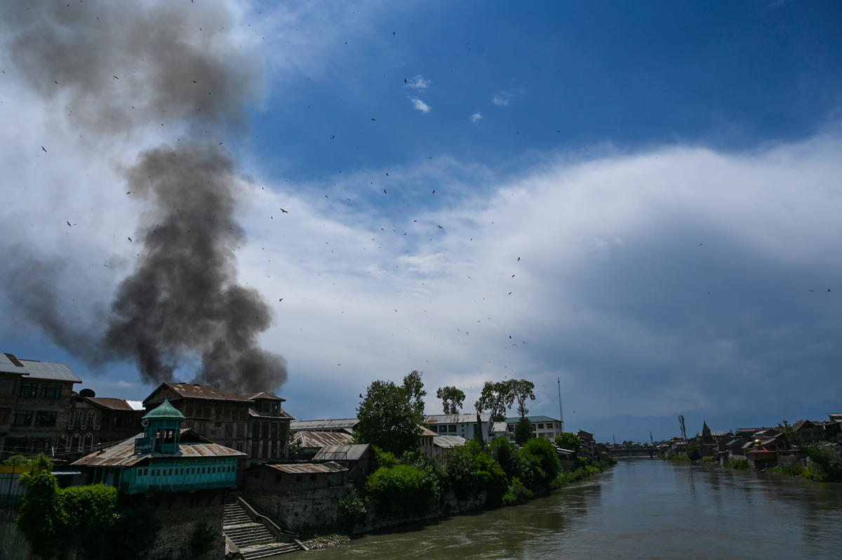Smoke rises from a house at the site of a gun battle between rebels and government forces in Srinagar. [Tauseef Mustafa/AFP]