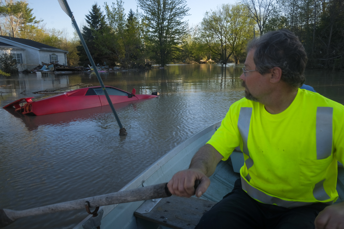 Neil Hawk and his wife Dawn take a rowboat out to a residential part of Sanford to inspect the damage to their neighbourhood in Sanford, Michigan. [Matthew Hatcher/Getty Images/AFP]
