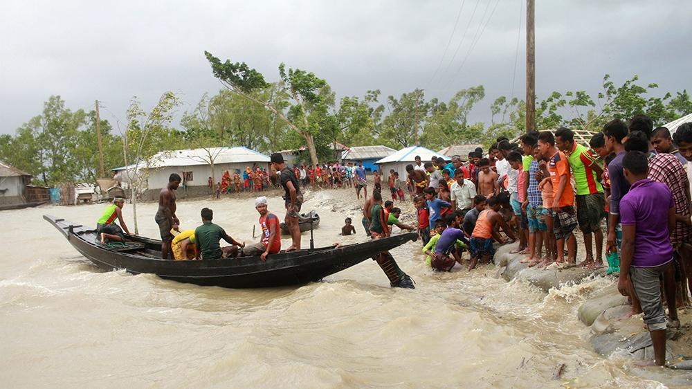 In this Wednesday, May 20, 2020 photo, people check an embankment before Cyclone Amphan made landfall, in Shyamnagar, Shatkhira, Bangladesh. A powerful cyclone that slammed into coastal India and Bang