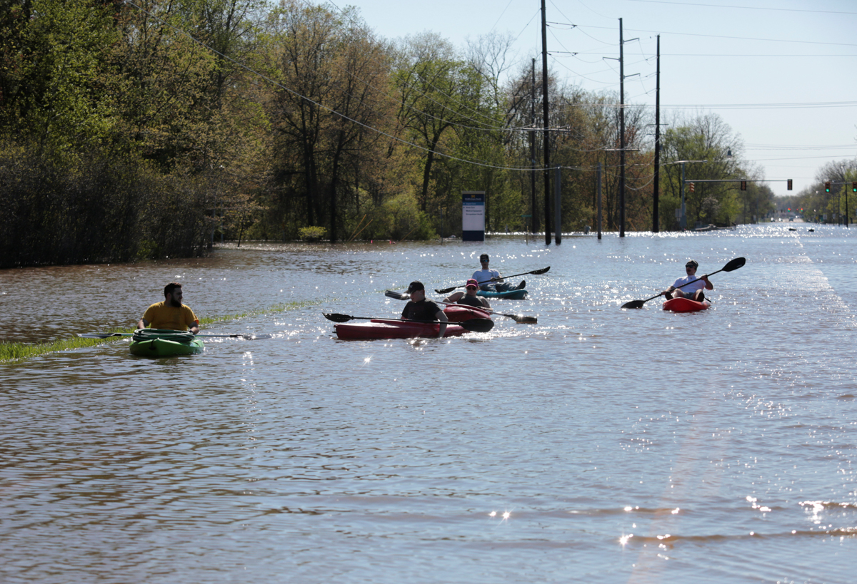 Residents paddle kayaks along a flooded street along the Tittabawassee River in Midland. [Rebecca Cook/Reuters]