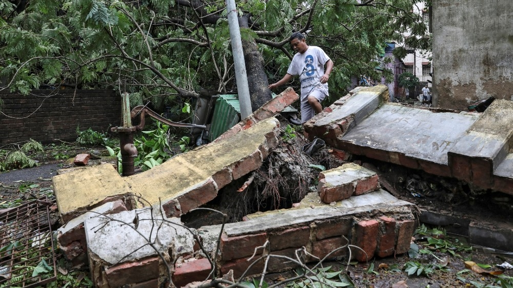A man walks over a collapsed wall after Cyclone Amphan in Kolkata