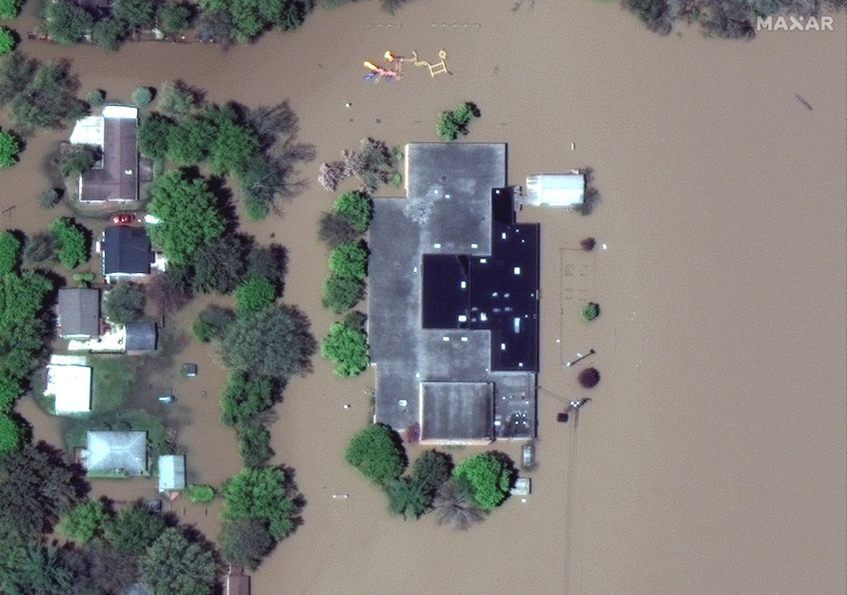 A satellite image shows a flooded Windover High School after rising floodwaters unleashed by two dam failures submerged parts of Midland, Michigan. [Handout: Maxar Technologies via Reuters]