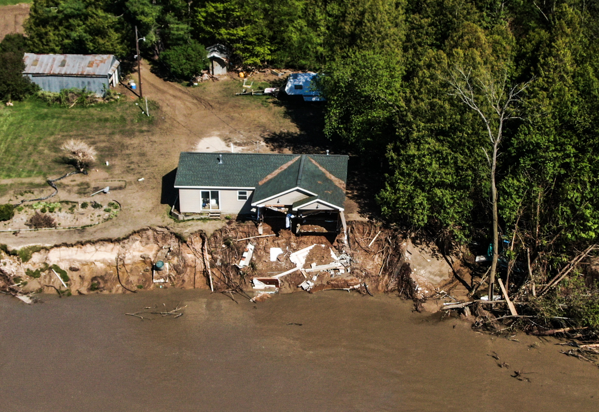 A damaged house is seen after the Edenville dam was breached near Edenville, Michigan. [Tannen Maury/EPA]