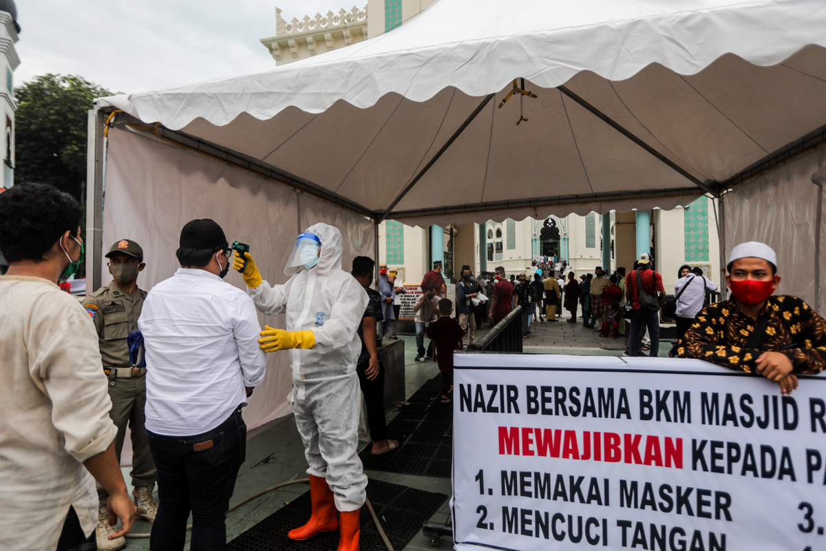 epa08440338 An health official wearing a protective suit checks the body temperatures of people before attending Eid al-Fitr prayers amid the coronavirus pandemic, at Al Mashun Grand Mosque in Medan,