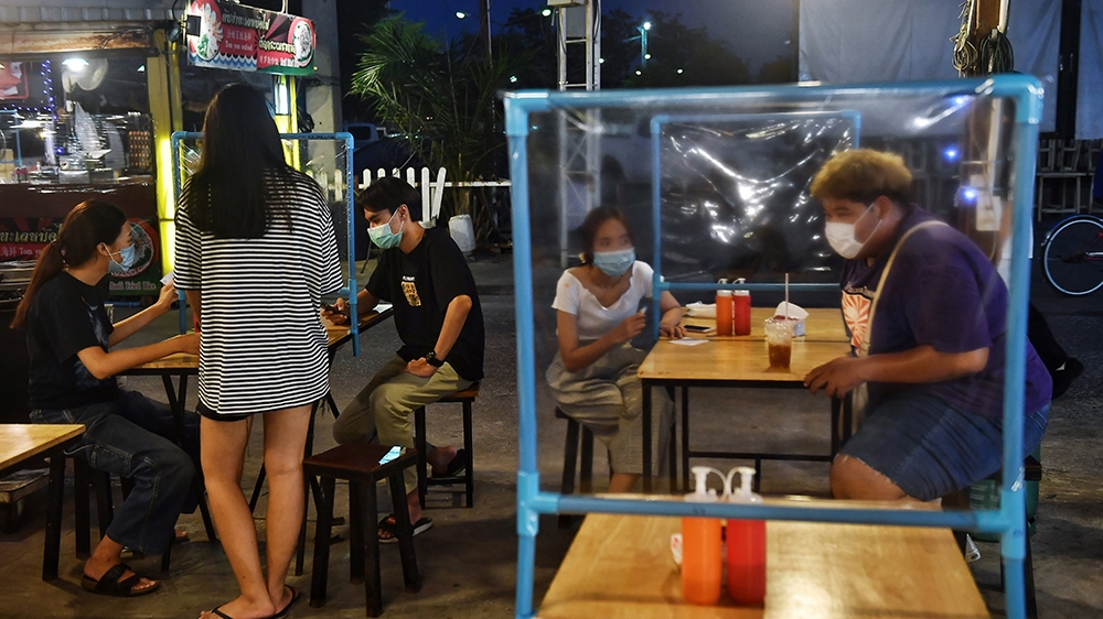 This picture taken on May 22, 2020 shows people eating at tables with plastic dividers, as a preventive measure against the spread of the COVID-19 novel coronavirus, at the Srinagarindra Train Night M