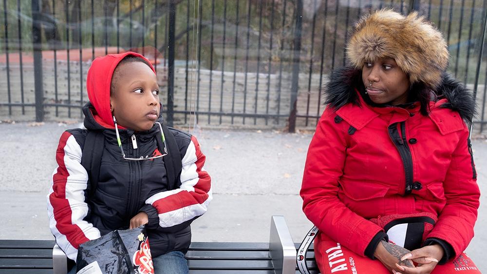 Still Here - Kamilah and Jeyson waiting for the bus [Sara Bennett/Al Jazeera]