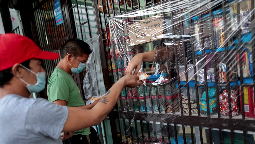 Shops install a makeshift plastic barrier as a protection from coronavirus disease, in Quezon City
