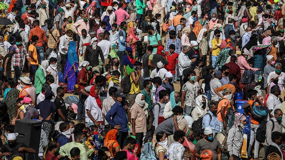 epa08436058 Indian migrant laborers queue for busses organized by the Brihanmumbai Municipal Corporation to get them to the Boriwali railway station where they can catch trains to their home villages,