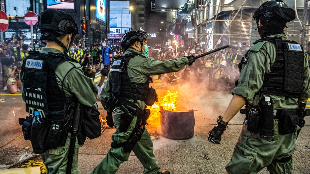 Police stand guard on a road to deter pro-democracy protesters from blocking roads in the Mong Kok district of Hong Kong on May 27, 2020, as the city's legislature debates over a law that bans insulti