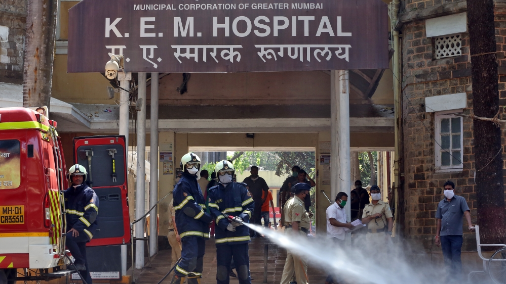 Firefighters disinfect the exteriors of a government-run KEM hospital, Mumbai
