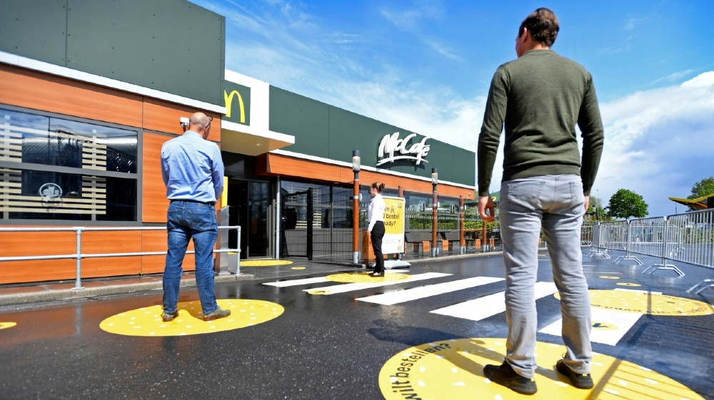 Customers wait outside on social distancing markings at a prototype location of fast food giant McDonald's for restaurants which respect the 1.5m social distancing measure,