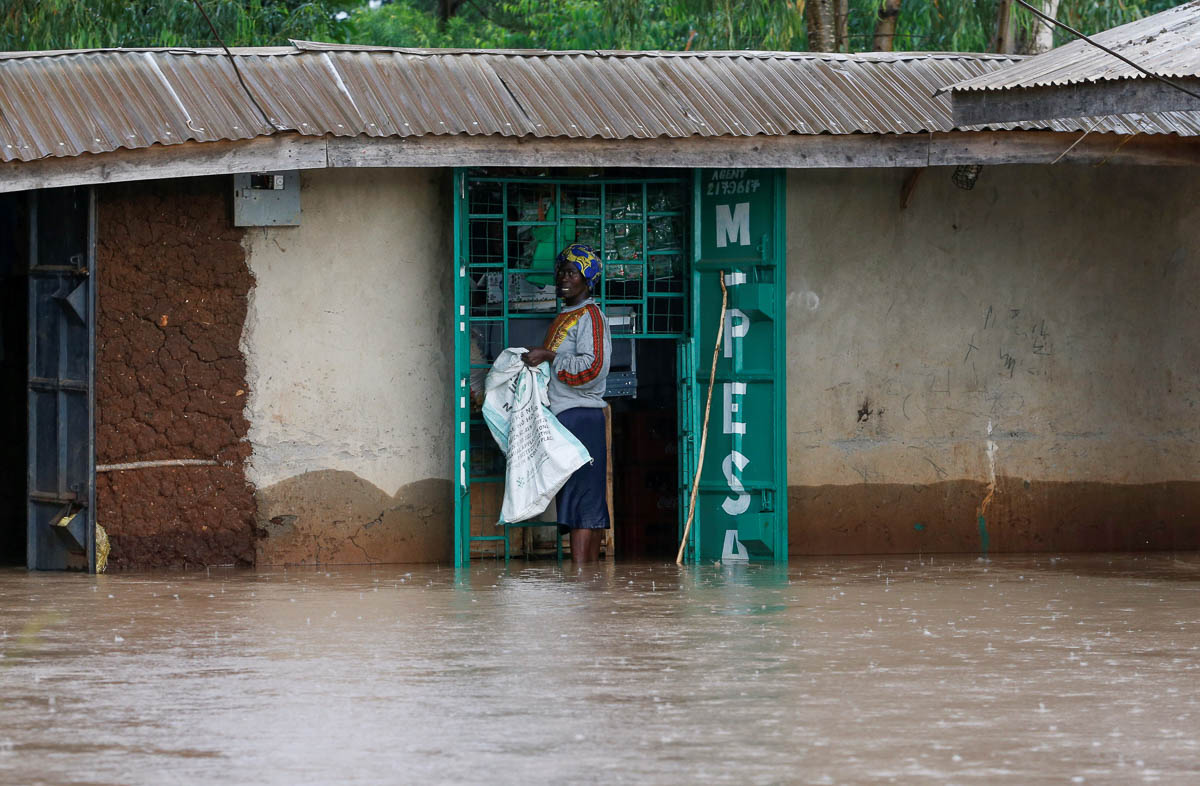 A woman stands in floodwaters next to a shop in Buyuku village of Budalangi, in Busia county. [Thomas Mukoya/Reuters]