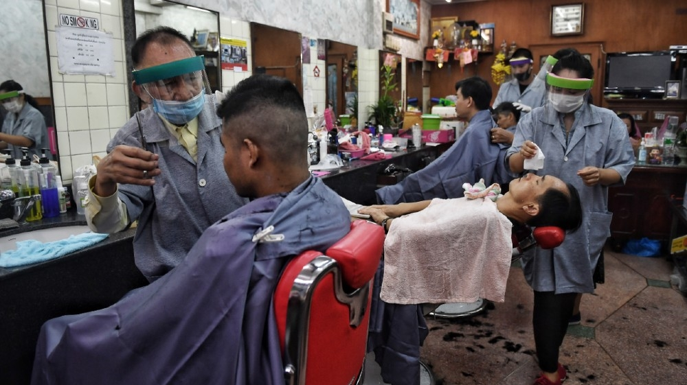 Hairdressers wear face shields and masks as they tend to customers at a barbershop in Bangkok on May 3, 2020, after it reopened due to an easing of measures to combat the spread
