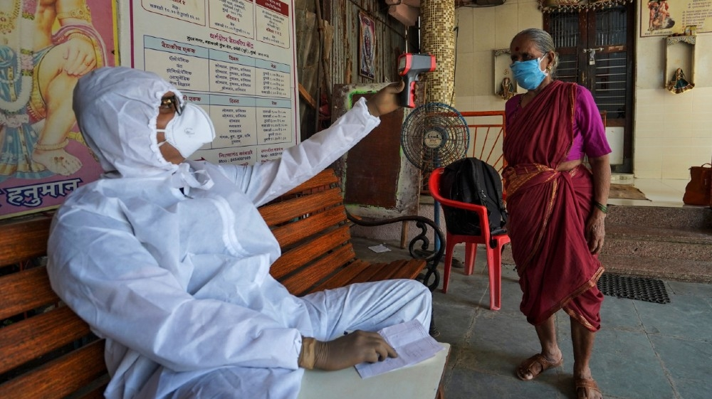Sanjay Meriya, 30, also known as the Spindoctor, wearing a protective gear checks temperature of a woman in a temporary health center where he coaches slum dwellers on the precautions