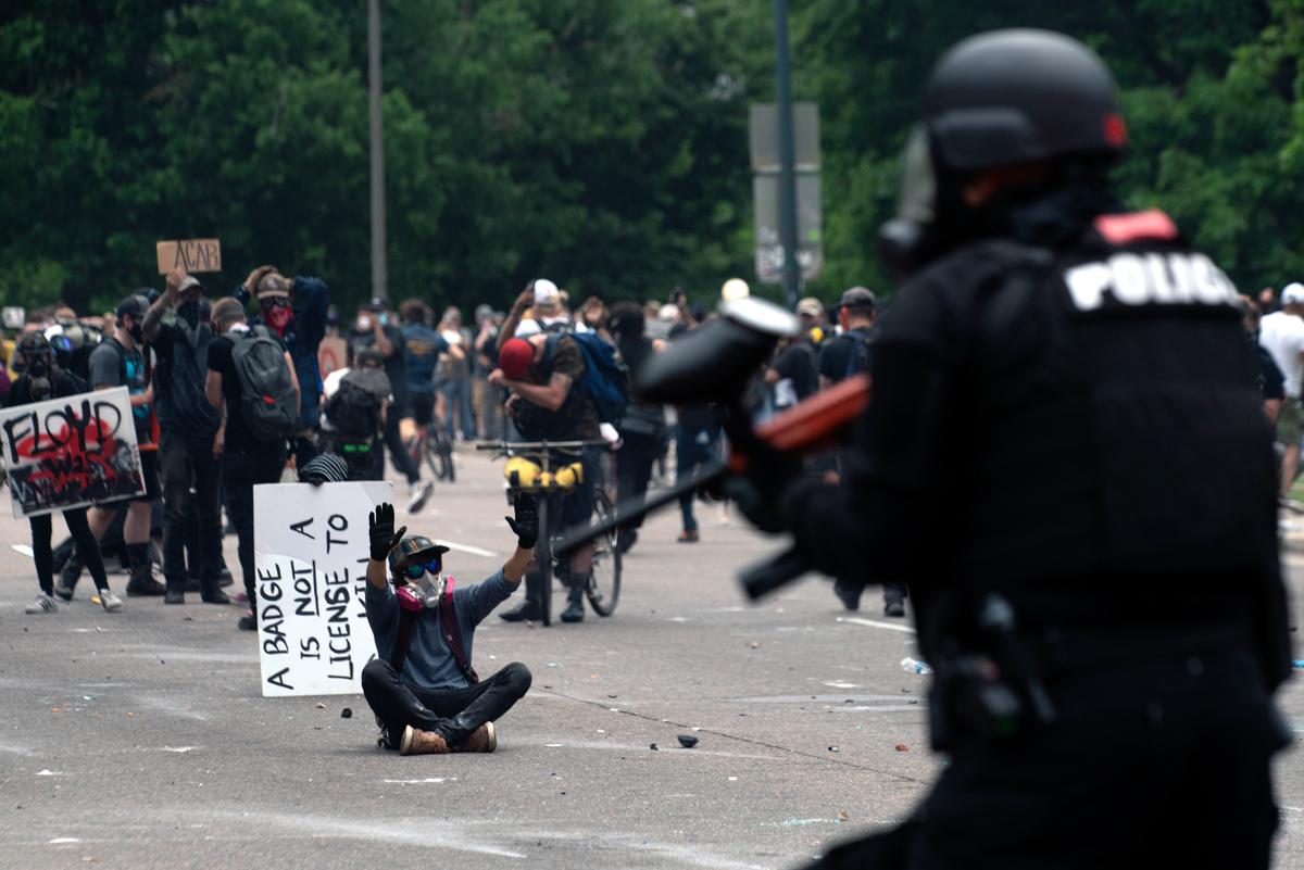 A demonstrator faces off with police officers during a protest in Denver, Colorado. [Jason Connolly/AFP]