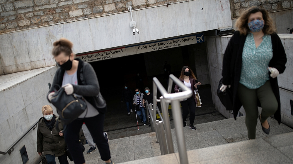 Commuters wearing protective face masks exit the metro station on Syntagma square, on the first day of easing of a nationwide lockdown against the spread of coronavirus disease (COVID-19), in Athens,