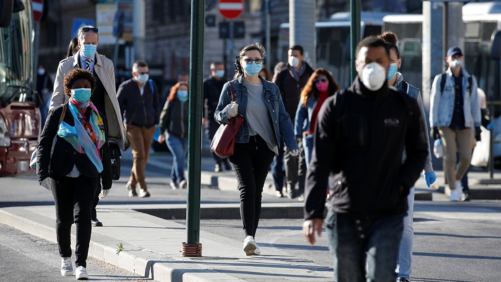 People wearing protective masks walk on a street, as Italy begins a staged end to a nationwide lockdown due to the spread of the coronavirus disease (COVID-19), in Rome, Italy May 4, 2020. REUTERS/Rem