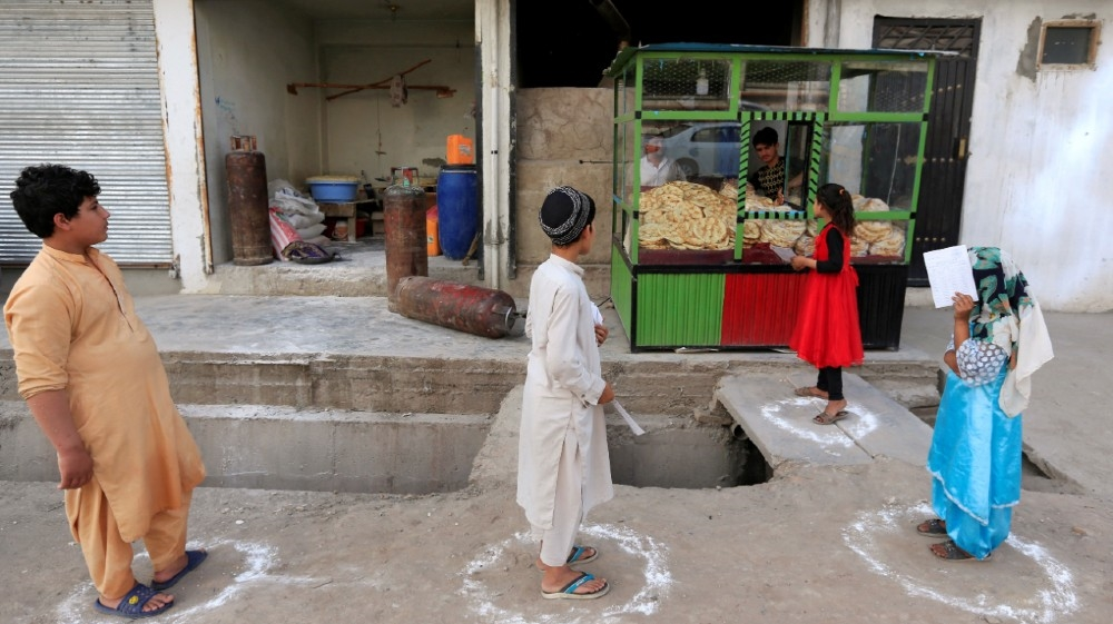 Afghan youths stand on social distancing markers as they buy bread from a bakery, amid the spread of the coronavirus disease (COVID-19), in Jalalabad, Afghanistan May 8, 2020. REUTERS/Parwiz
