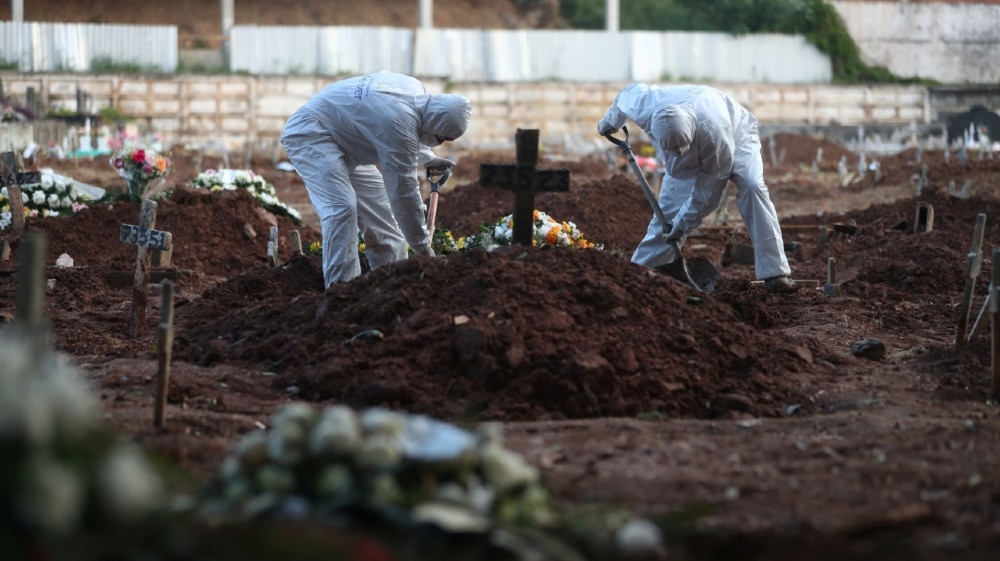 Gravediggers wearing protective garments work as relatives of Neide Rodrigues, 71, who died of the coronavirus disease (COVID-19), attend her burial at a cemetery in