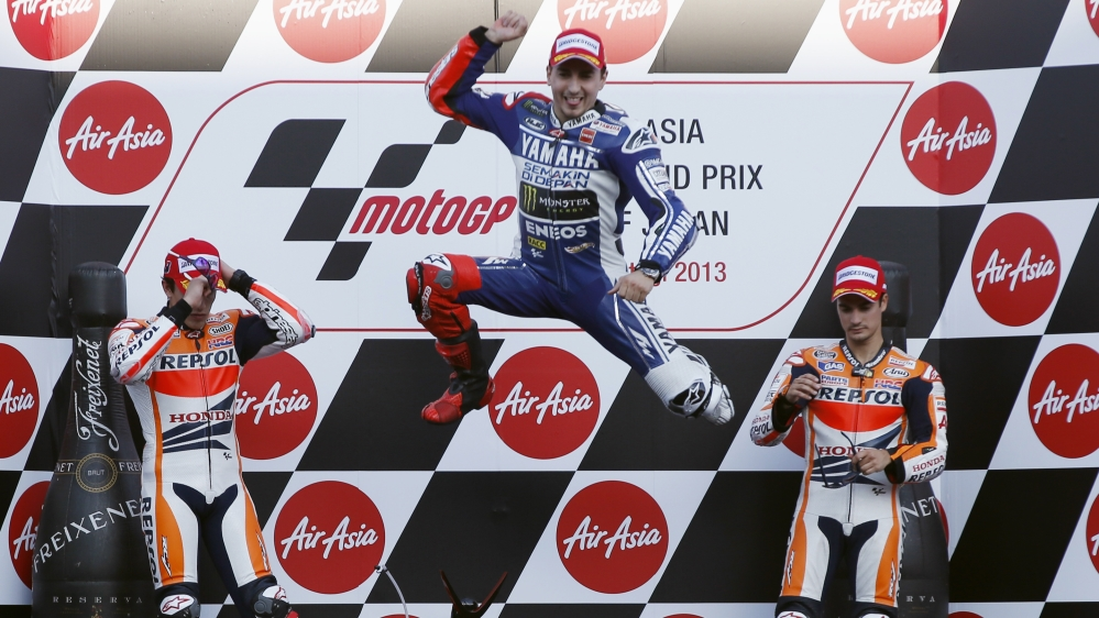 Yamaha MotoGP rider Lorenzo of Spain jumps into the air as he celebrates winning the Japanese Grand Prix next to Honda MotoGP rider Marquez of Spain and Pedrosa of Spain on the podium in Motegi