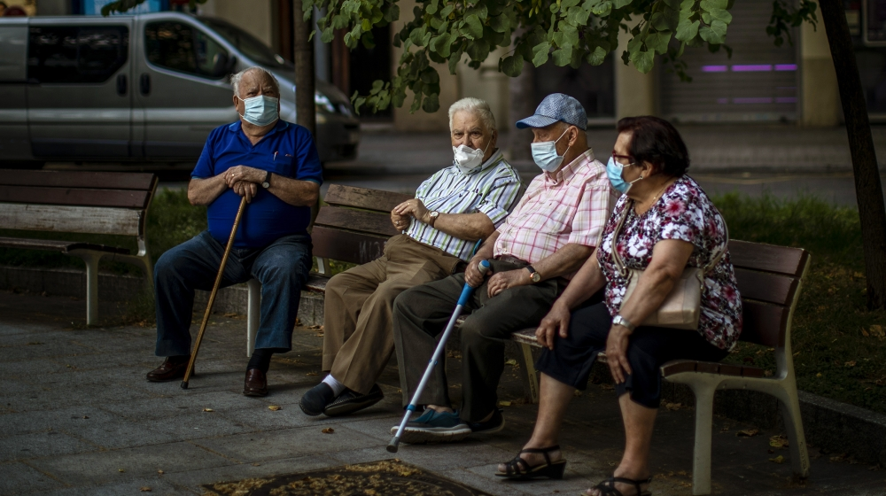 Elder people wearing face masks sit on a bench in a square in Barcelona, Spain, Sunday, May 31, 2020. Spanish Prime Minister Pedro Sánchez says he will ask Spain's Parliament for a final two-week ext