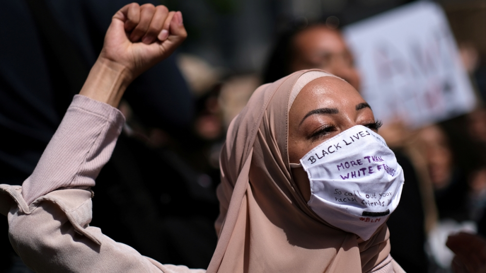 A woman wearing a face mask raises her fist during a protest against the death in Minneapolis police custody of African-American man George Floyd, at Hermannplatz square in Neukoelln district, Berlin,