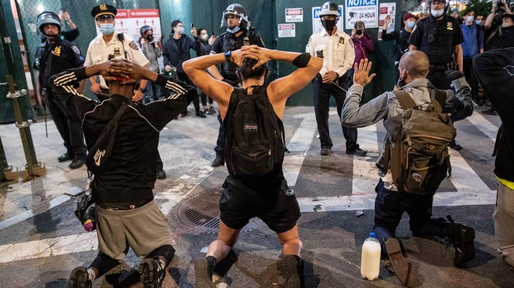 Protesters kneel in front of New York City Police during a march to honor George Floyd in Manhattan on May 31, 2020 in New York City. Protesters demonstrated for the fourth straight night after video