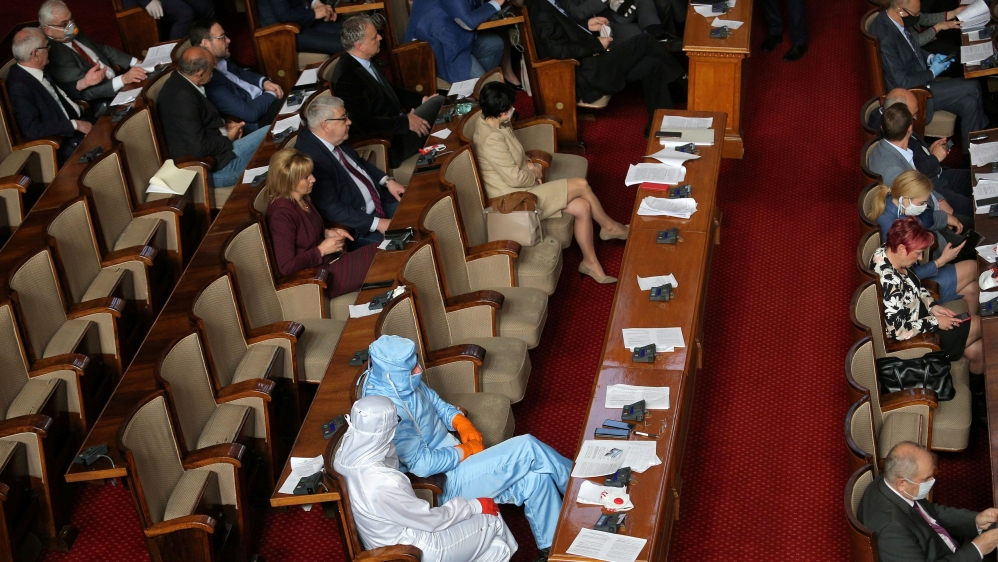 Leader of Bulgarian party Volya, Mareshki, and a deputy from his party wear protective suits during debates in the parliament in Sofia