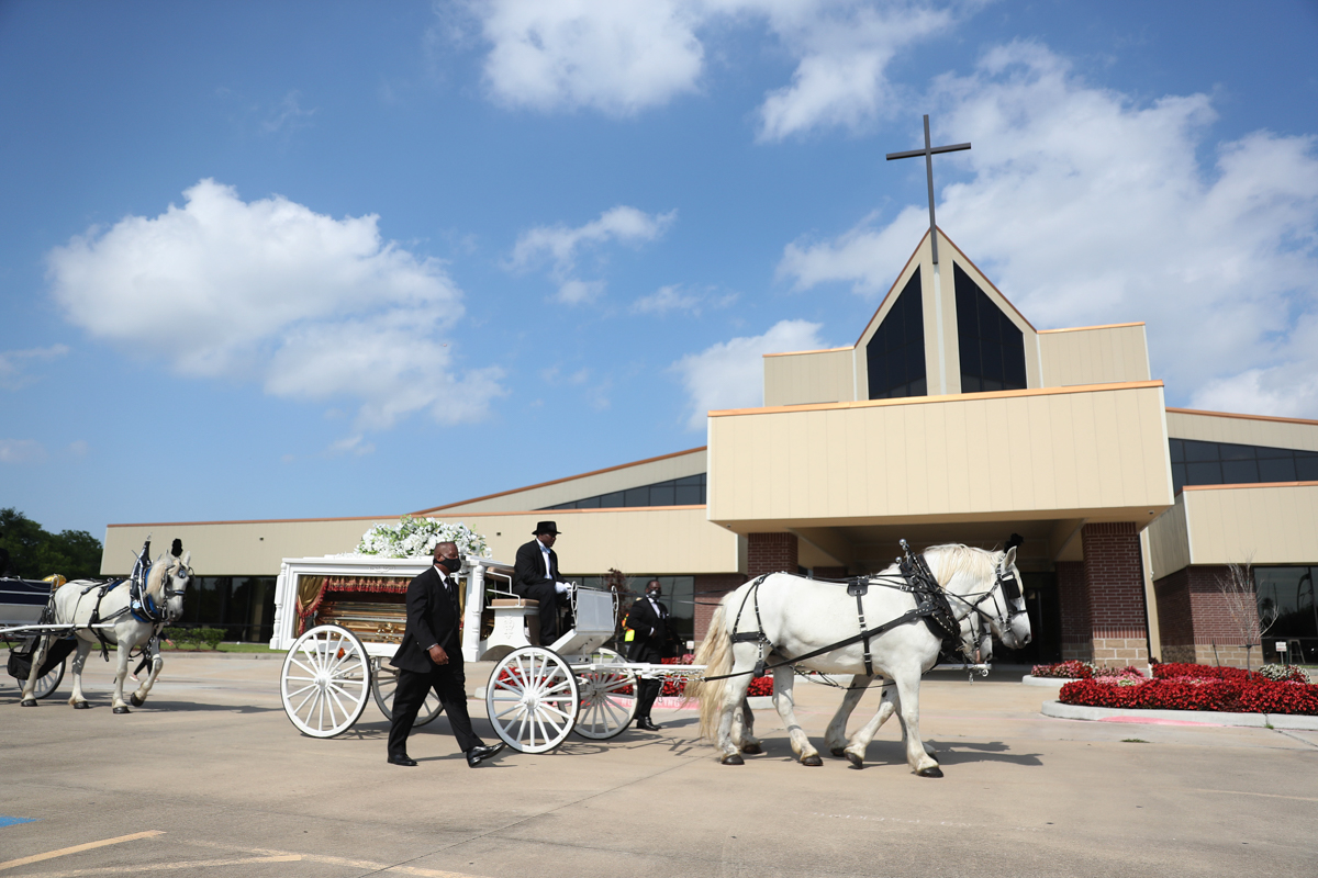 """Terence Reed, Jr drives his horse-drawn hearse carrying the remains of George Floyd to the Houston Memorial Gardens cemetery. On the way, the cortege passed hundreds of well-wishers who chanted Floyd's name. """"Rest in power"""" was scrawled in blue chalk on the road, while one held up a sign saying: """"We will never forget."""" [Joe Raedle/Getty Images/AFP]"""