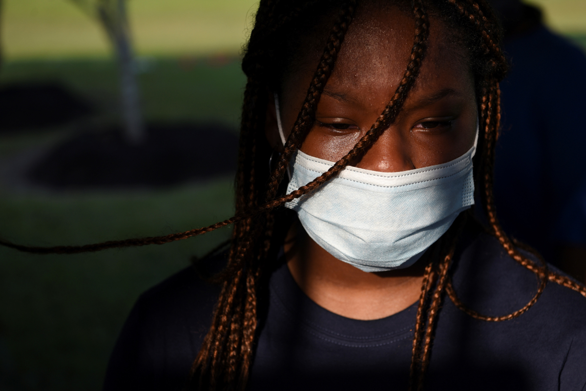 A young woman sheds a tear at the gravesite of George Floyd. The Fountain of Praise was the final stage in a series of ceremonies before Floyd's coffin was conveyed by horse-drawn carriage in the early evening to his final resting place by his mother's grave. [Callaghan O'Hare/Reuters]
