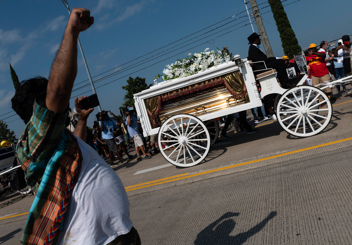 A man raises his fist as mourners watch the casket of George Floyd being carried by a white horse-drawn carriage to his final resting place at the Houston Memorial Gardens cemetery in Pearland, Texas. [Andrew Caballero-Reynolds/AFP]
